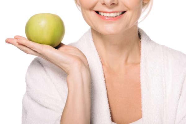 Frau mit schönen Zähnen hält Apfel. Gesunde Ernährung ist wichtig für gesunde Zähne.
