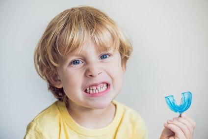 Ein kleines Kind zeigt seine Zähne und hält eine Zahnspangenschiene in der Hand. Schon bei kleinen Kindern kann eine kieferorthopädische Behandlung notwendig sein.